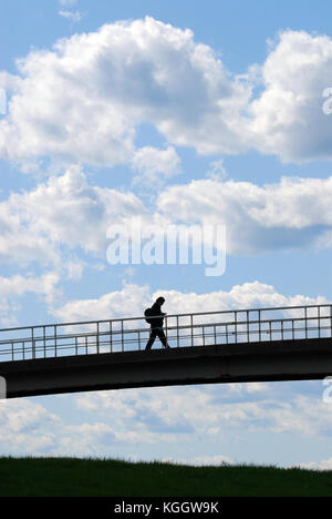 Millennial on the move, holding smartphone, crossing bridge. Silhouette of young man against clear blue sky. - Stock Photo