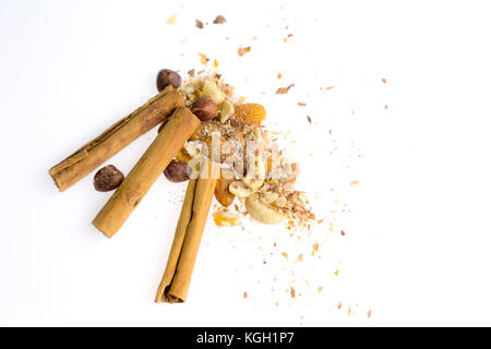Heap of nuts and cinnamon sticks on white. Christmas dessert food baking ingredients. Cinnamon rolls, almonds, hazelnuts, - Stock Photo