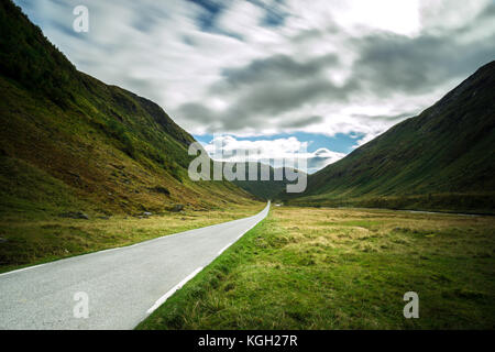 Straight mountain road leading through dramatic valley, Norway. - Stock Photo
