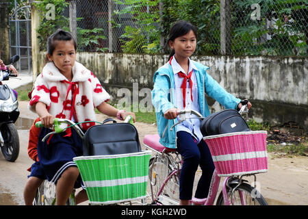BINH DINH, VIET NAM- NOV 3, 2017:Group of Vietnamese children coming home from school by bicycle, crowd Asian little - Stock Photo