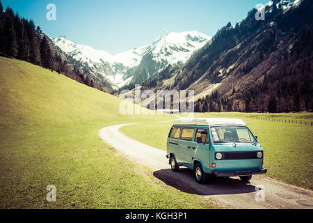 Vintage VW Bully camping car driving on mountain valley road - Stock Photo