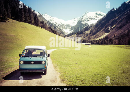 OBERSTDORF, BAVARIA, GERMANY - MAY 10, 2017: Vintage blue and white VW Bully camping car driving on mountain valley - Stock Photo