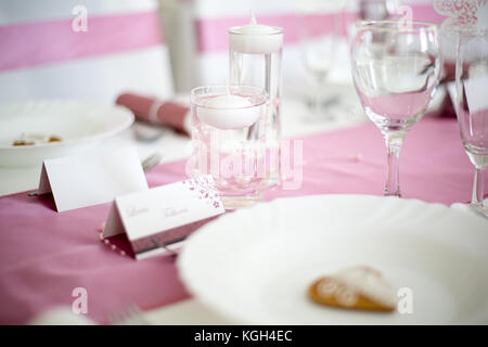 Pink and white wedding table with small round white tea candle in a clear glass, pink runner, empty wine glasses, - Stock Photo