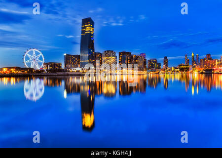 BLue dark sunset at Melbourne Dockalnds area with still Yarra river waters mirroring bright lights of modern ubran - Stock Photo