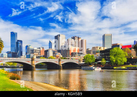 Princes bridge in Melbourne city across Yarra river on a sunny day in view of high-rise towers and modern urban architecture.