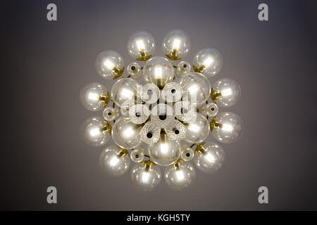 Crystal glass chandelier view from bottom, round shape, round glass bulb covers, lit, energy-efficient light bulbs - Stock Photo