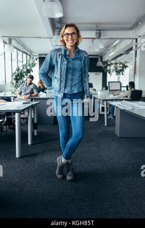 Young female manager standing in office with colleagues working in background. Happy businesswoman looking at camera - Stock Photo