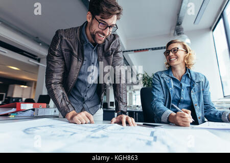 Business partners working together in office. Two architects working on construction plan. - Stock Photo