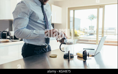 Man in formal clothes making coffee using French press with a laptop computer on kitchen table. Businessman preparing - Stock Photo