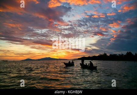 Fishermen on their way to their traditional suspended fishing nets in the sea, at the entrance to Thu Bon River, - Stock Photo