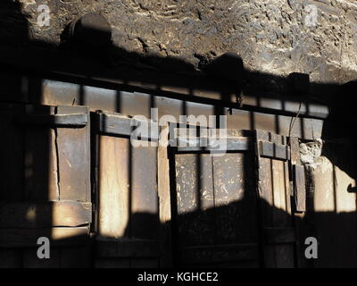 Abstract background of a combination of wooden and stone surfaces with spots of light and shadow. - Stock Photo