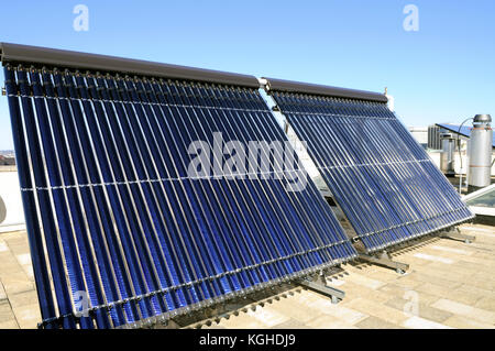 Evacuated tube solar collector panels on rooftop - Stock Photo