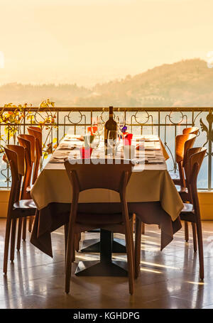 Table in italian restaurant served with a bottle of wine and wine glasses - Stock Photo