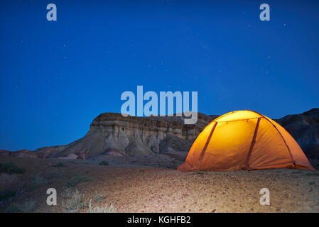 Lonely evening camping in Mongolian canyons. yellow illuminated tent is located near canyons - Stock Photo