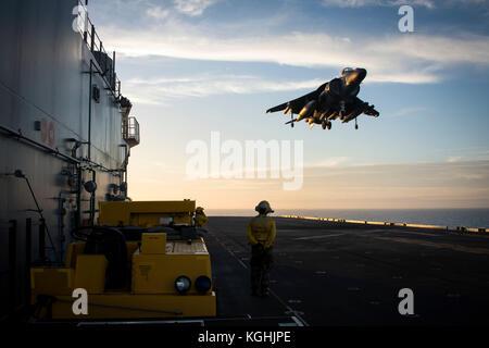 An AV-8B Harrier II jet lands on the flight deck of the amphibious assault ship USS Iwo Jima (LHD 7) - Stock Photo