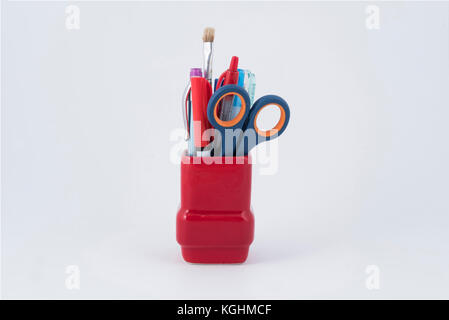 some pens, brush and a pair of scissors in a red pen holder - Stock Photo
