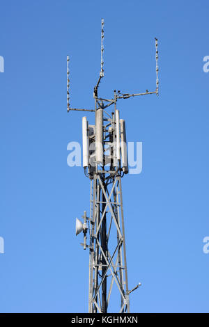 Telecommunications repeater tower against a clear blue sky - Stock Photo