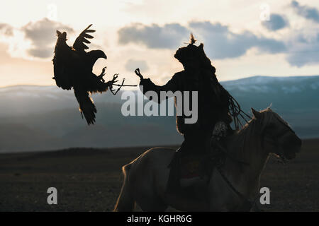 Silhouette of the Eagle Hunter traditional clothing, while hunting with a golden eagle in desert mountain of Western - Stock Photo