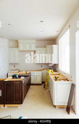 Custom kitchen cabinets in various stages of installation base for island in center - Stock Photo