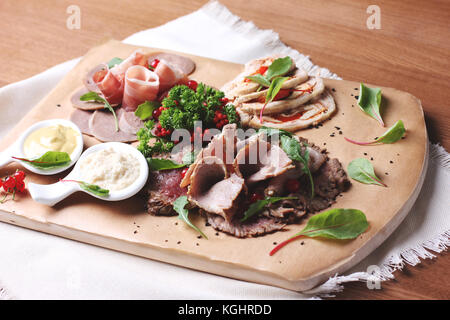 Cold smoked meat plate with greens and mustard on wooden board - Stock Photo