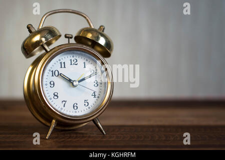golden time clock - Golden bell clock on a wooden table background - Stock Photo