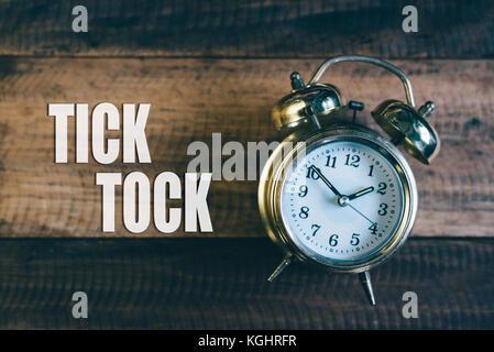 tick tock day concept - golden bell clock on a wooden table background with 'Tick Tock' word - Stock Photo
