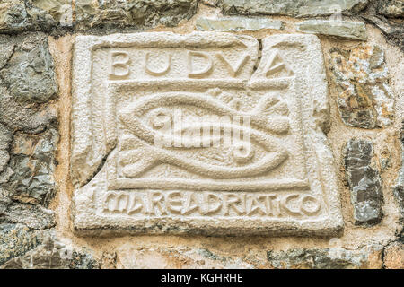 Two fish - a symbol of the city of Budva, Montenegro. The historical symbol of Budva on the wall of an ancient citadel. - Stock Photo