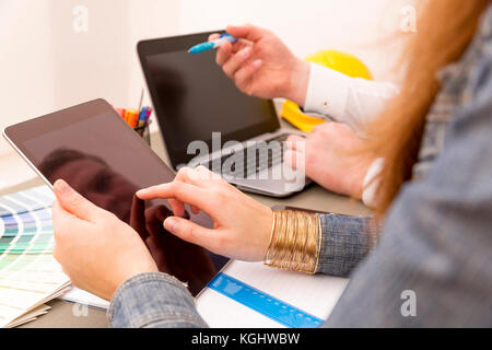 Creative interior design team during brainstorming working on laptop in office - Stock Photo