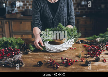 florist making Christmas wreath  - Stock Photo