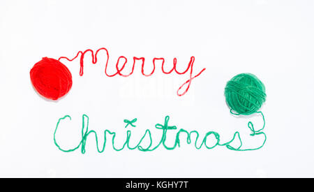 Merry Christmas written in cursive with red and green yarn and photographed from above against a white background. - Stock Photo
