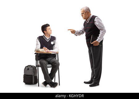Teacher scolding a teenage student seated in a school chair isolated on white background - Stock Photo
