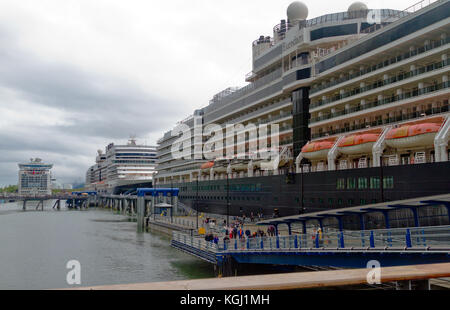 People disembarking from the cruise ship Eurodam in Juneau, Alaska with several other cruise ships in the background. - Stock Photo