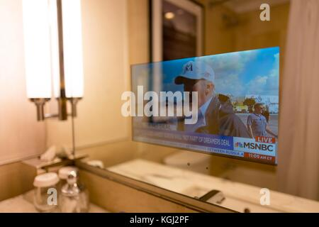 At a business hotel in Manhattan, New York City, New York, a transparent television built into the bathroom mirror - Stock Photo