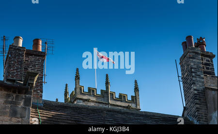 England flag cross of St George on a church tower between two chimneys under a clear blue sky at Barnard Castle, - Stock Photo