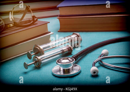 Medicine books next to syringes vintage and stethoscope, concept of medicine - Stock Photo