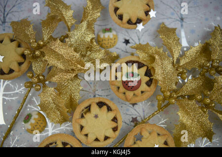 Christmas food photography picture with traditional pastry fruit mince pies with seasonal iced decorations and silver - Stock Photo