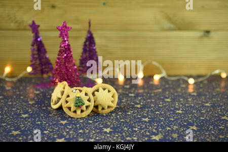 Christmas food photography image of traditional English mince pies with iced tree on top and glitter tree decorations - Stock Photo