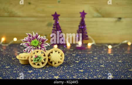 Christmas food photography image of traditional English mince pies with winter flower and glitter tree decorations - Stock Photo