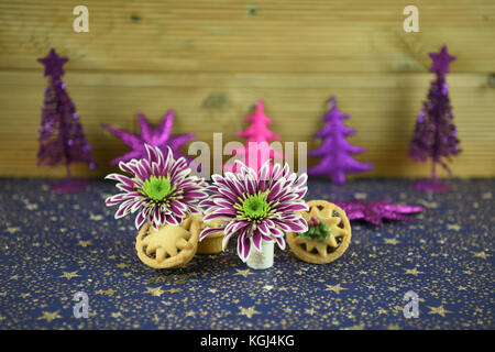 Christmas food photography image of traditional English mince pies with winter flowers and sparkly glitter tree - Stock Photo