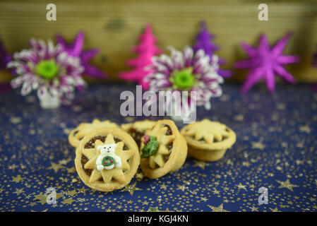 Christmas food photography image of traditional English mince pies with cute polar bear iced decoration and glitter - Stock Photo