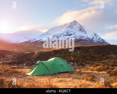 Green touristic tent on meadow at river below snowy cone of mountain Stob Dearg 1021 metres high. Higland in Scotland - Stock Photo