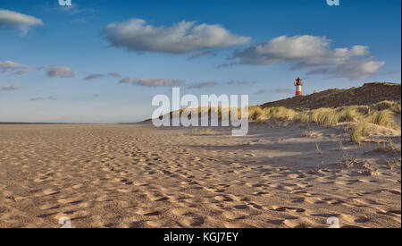 Deserted beach with lighthouse behind sand dunes in evening light in a low angle view showing tracks in the sand - Stock Photo