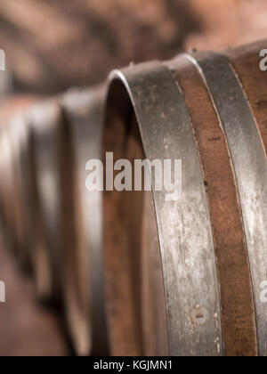 Wine barrels in row close up at cellar - Stock Photo