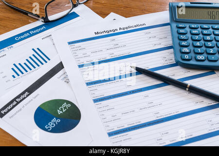 Mortgage application on desk with credit report, budget, calculator, pen and glasses - Stock Photo