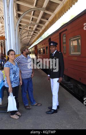 Peradeniya Junction Station Kandy Central Province Sri Lanka couple talking to guard - Stock Photo