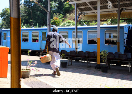 Peradeniya Junction Station Kandy Central Province Sri Lanka Man carrying basket rushing to catch train - Stock Photo