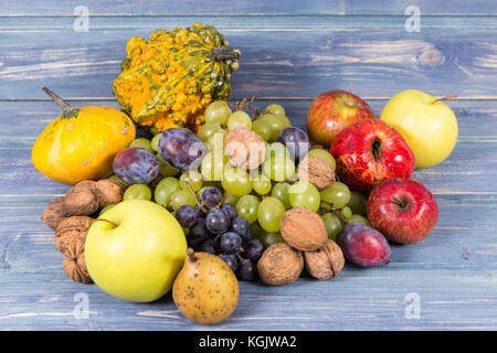 Bunch of autumn fruits on wooden background as fall harvest concept - Stock Photo