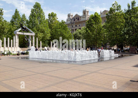 Tourists playing on n interactive fountain in front of the monument to the Hungarian victims of the Nazis in Budapest - Stock Photo