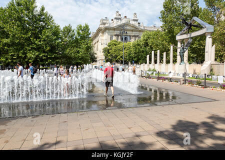 Square in Budapest with man walking through fountain. Monument to the Hungarian victims of the Nazis. - Stock Photo