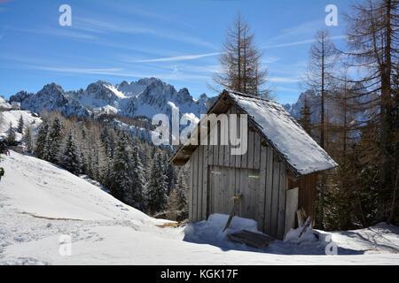 A small wooden hut in the snow on the slopes of Monte Lussari, Friuli Venezia Giulia, north east Italy - Stock Photo